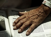 My mom's hand on the newspaper, by Xosé Castro, with Creative Commons licence